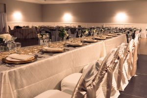 white and gold bridal table with floral arrangements and high end silverware