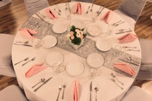pink and white place settings on a round table