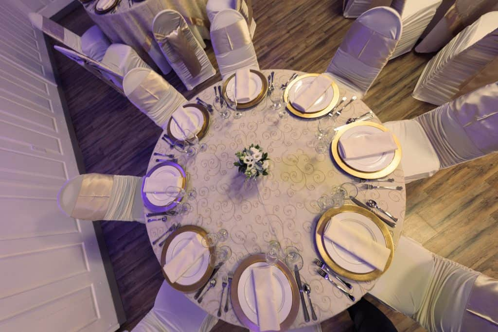 table with white linens and gold plates